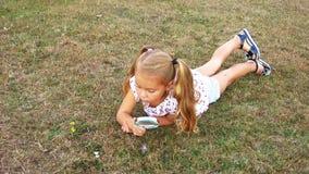 A menina encontra-se em um gramado com uma lupa Uma menina olha através de uma lupa Menina bonita que guarda uma lupa filme