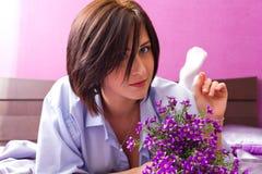 A menina encontra-se em uma cama ao visor com flores Fotografia de Stock Royalty Free