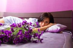 A menina encontra-se em uma cama com descanso e flores Imagens de Stock Royalty Free