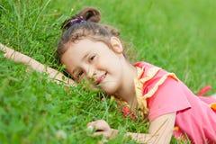 A menina encontra-se em uma grama Foto de Stock Royalty Free