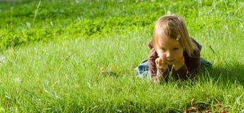 A menina encontra-se na grama Fotos de Stock