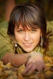 A menina encontra-se na terra no parque do outono Fotos de Stock