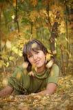A menina encontra-se na terra sob as folhas de outono Foto de Stock Royalty Free