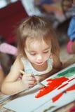 A menina encontra-se no assoalho do quarto e na imagem da pintura Fotos de Stock Royalty Free