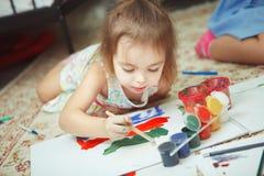 A menina encontra-se no assoalho do quarto e na imagem da pintura Imagens de Stock