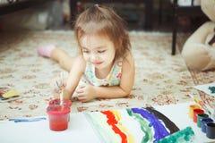 A menina encontra-se no assoalho do quarto e na imagem da pintura Imagem de Stock