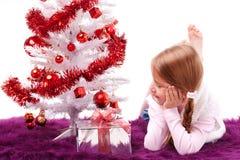 A menina encontra-se sob a árvore de Natal Foto de Stock Royalty Free