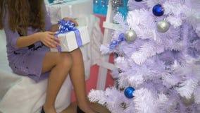 A menina encontra um presente sob a árvore de Natal video estoque