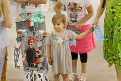 A menina encontrou-se com um robô mecânico na exposição de desenhistas novos do técnico Foto de Stock