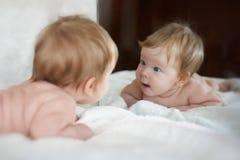A menina encontrou um amigo novo na reflexão de espelho Foto de Stock