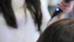 A menina endireita o cabelo em um cabeleireiro vídeos de arquivo