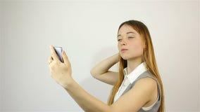 A menina endireita seu cabelo e olha o telefone vídeos de arquivo