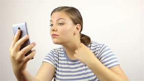 A menina endireita seu cabelo e olha o telefone video estoque