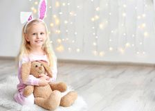Menina engraçada bonito com as orelhas do coelho e o brinquedo peluches que sentam-se no assoalho Imagem de Stock