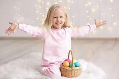 Menina engraçada bonito com a cesta completa dos ovos da páscoa que sentam-se em casa fotos de stock