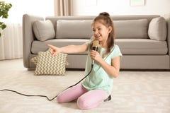 Menina engraçada bonito com microfone fotos de stock royalty free