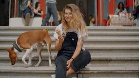 A menina engraçada bonito come o gelado com cão vídeos de arquivo