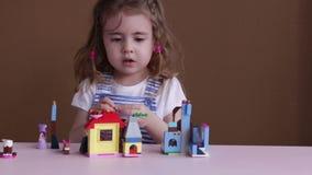 A menina engraçada bonito da criança em idade pré-escolar que joga com brinquedo da construção obstrui a construção de uma torre  filme