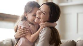 Menina engraçada bonito de sorriso de abraço de riso de amor da criança da mãe nova imagem de stock