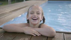 Menina engraçada bonito do retrato com tranças que ri a vista na câmera O polegar da exibição da criança acima da vista fora do video estoque