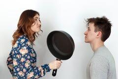 Menina engraçada com o homem do xingamento da frigideira Imagem de Stock Royalty Free