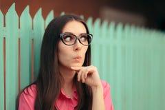 A menina engraçada com vidros do Gato-olho que pensa a fatura planeia Fotografia de Stock