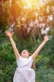 A menina engraçada da criança corre, saltos e joga um ramalhete das flores no fundo exterior da natureza fotografia de stock royalty free