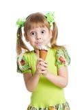 Menina engraçada da criança que come o gelado isolado Imagem de Stock
