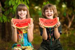 A menina engraçada das irmãs mais nova come a melancia no verão fotos de stock royalty free
