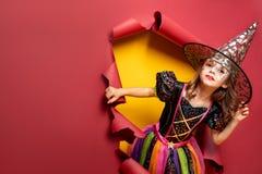 Menina engraçada de riso da criança em um traje da bruxa no Dia das Bruxas imagens de stock royalty free
