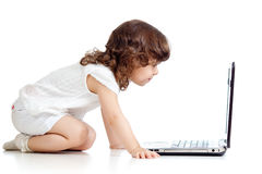 Menina engraçada do miúdo que olha o portátil Fotos de Stock Royalty Free