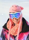 Menina engraçada do snowboard com chapéu do porco imagens de stock