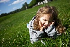 A menina engraçada encontra-se na grama verde Fotografia de Stock