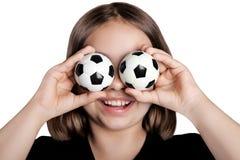Menina engraçada fechado seus olhos com bolas de futebol Imagem de Stock Royalty Free