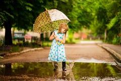 Menina engraçada feliz da criança com o guarda-chuva que salta em poças nas botas de borracha e no vestido do às bolinhas imagem de stock