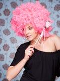 Menina engraçada na peruca cor-de-rosa que levanta para a câmera Imagens de Stock