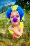 Menina engraçada na peruca do palhaço com nariz azul imagens de stock