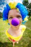 Menina engraçada na peruca do palhaço com nariz azul imagens de stock royalty free