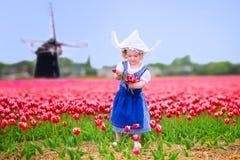 A menina engraçada no traje holandês nas tulipas coloca com moinho de vento Imagem de Stock