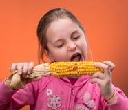 Menina engraçada que rectifica para morder o milho seco Fotos de Stock