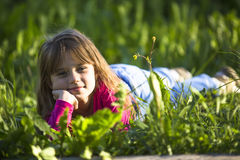 Menina engraçada pequena que encontra-se na grama verde felicidade Foto de Stock Royalty Free