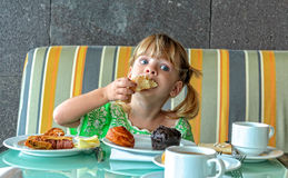 Menina engraçada que come o café da manhã Fotos de Stock