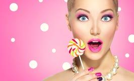 Menina engraçada que come o pirulito Fotos de Stock