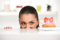 Menina engraçada que esconde atrás da tabela Imagem de Stock Royalty Free