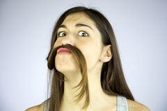 Menina engraçada que faz o bigode de seu cabelo Fotografia de Stock Royalty Free