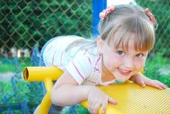 Menina engraçada que joga no campo de jogos. Imagem de Stock