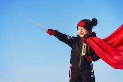 Menina engraçada que joga o super-herói do poder foto de stock royalty free