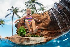 Menina engraçada que salta altamente na água foto de stock