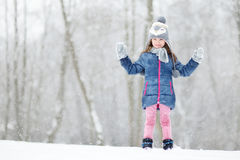 Menina engraçada que tem o divertimento no parque do inverno Fotografia de Stock
