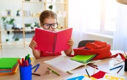 Menina engra?ada da crian?a que faz a escrita e a leitura dos trabalhos de casa em casa fotografia de stock royalty free